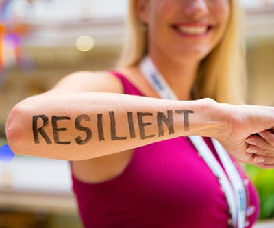"A arm with the word ""resilient"" across it"