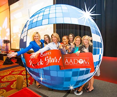 "AADOM members taking a photo around a prop that says ""Rock star AADOM"""