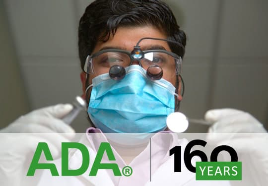 Male doctor wearing goggles and a mask holding dental instruments