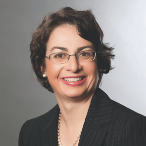 Ann-Marie Depalma wearing a black blazer and glasses against a gray background