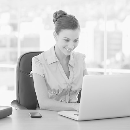 A young woman sitting in her office while typing on her laptop and smiling in black and white