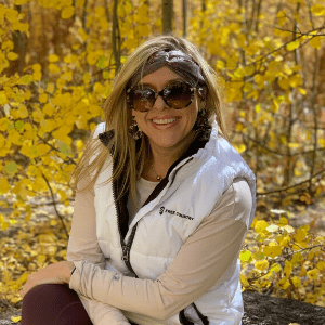 AADOM Author, Leslie Lytle FAADOM, in fall apparel with trees in the background, author of blog on career enhancement as a dental office manager.