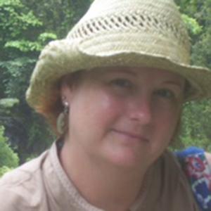 Jenn Randall in a straw hat outside