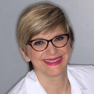 Rosa Pasquantonio, FAADOM smiling with pink lipstick, glasses, and a white shirt