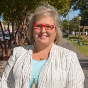 Monica Payne in red glasses, blue top, and white blazer