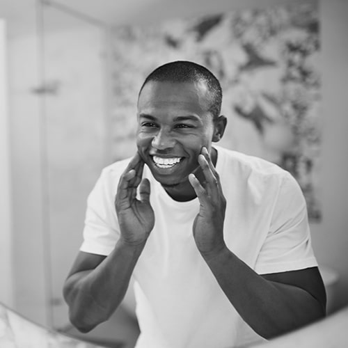 A young man smiling in the mirror