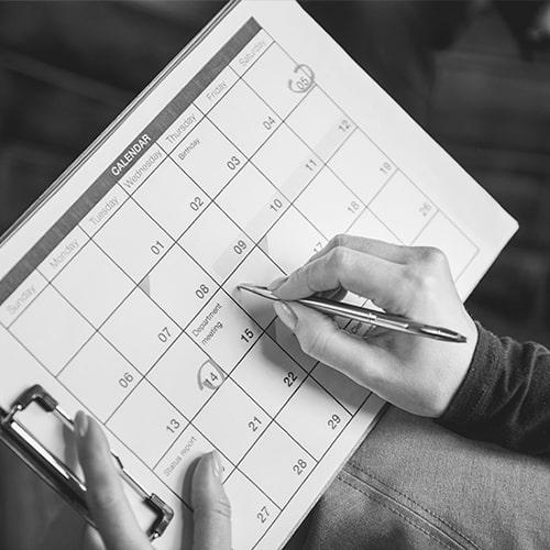 A person using a calendar to create a schedule