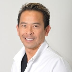 Dr. Chuck Le in white dentist coat
